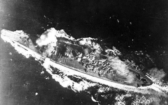 The Japanese battleship Yamato is hit by a bomb near her forward 460mm gun turret during attacks by U.S. carrier planes as she transited the Sibuyan Sea.