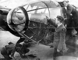 A RAF corporal examines the bullet holes in the cockpit of a German He 111