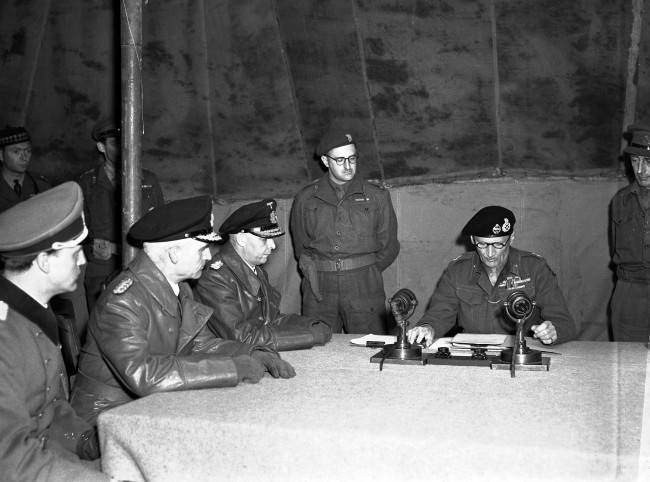 Field Marshal Bernard Montgomery reads over the surrender pact to senior German officers, from left, Major Friedel, Rear Admiral Wagner and Admiral Hans-Georg Von Friedeburg