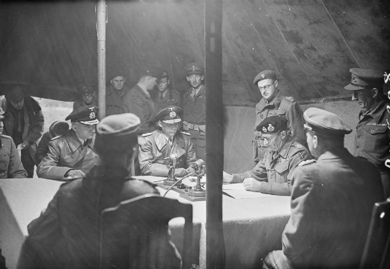 """Field Marshal Bernard Montgomery signing the Instrument of Surrender of the German Armies in the northern part of Germany at Lüneberg Heath """"Timeloberg""""."""